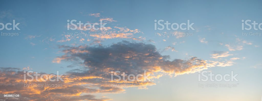 Early Clouds Reflecting Sunrise Light with Blue Skies in the background - Royalty-free Blue Stock Photo