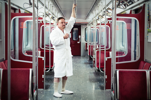 Early commuter wearing bathrobe and slippers on the underground train.