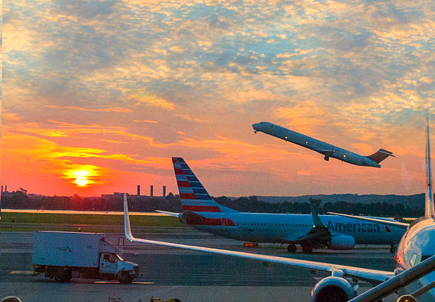 Early departure Washington D.C., USA - July 26, 2016: Delta Airlines jet takes off as an American Airlines planes taxis out for an early morning departure from Reagan National Airport in Washington D.C. ronald reagan washington national airport stock pictures, royalty-free photos & images