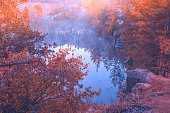 Early foggy morning. Sunrise over a lake with a rocky shore. Nature landscape in autumn