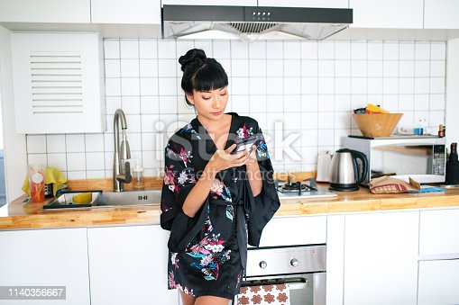 Young beautiful Asian woman texting on the phone, standing in the kitchen