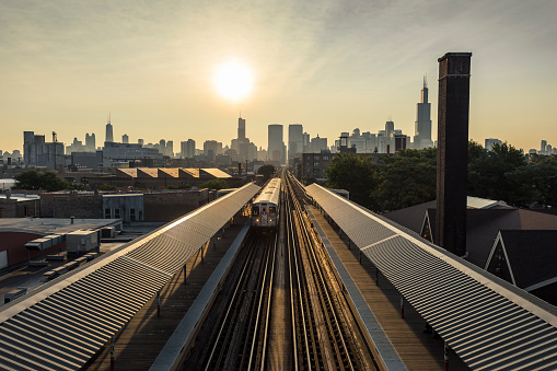 Early morning Chicago skyline with train and sun