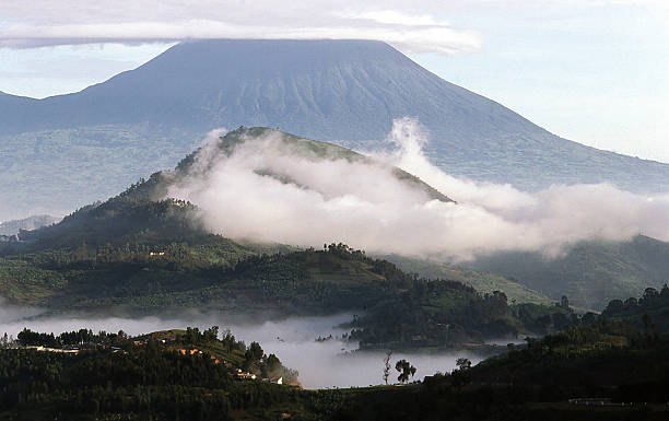 Early Morning Clouds Lifting over Virunga Volcanoes Rwanda Early Morning Clouds Lifting over Virunga Volcanoes Rwanda lenticular cloud stock pictures, royalty-free photos & images