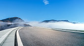 In the early morning, the road crosses the foggy mountains, Inner Mongolia, China.