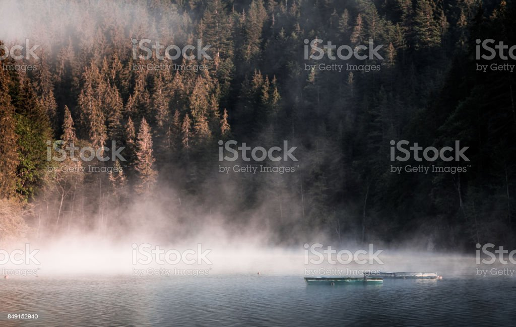 Early morning lake with mist, forest and rowing boats stock photo