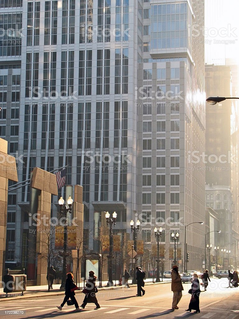 Early Morning Pedestrians Crossing Sun Drenched Downtown Street royalty-free stock photo