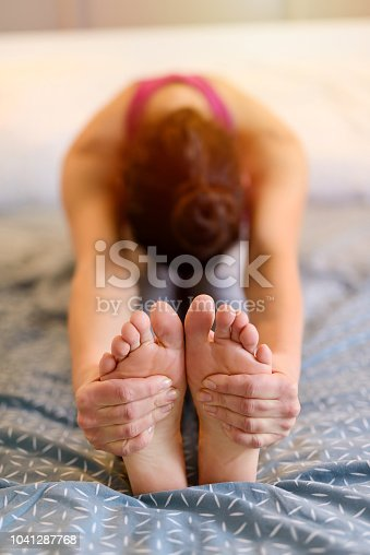 901404510istockphoto Early morning stretching. Picture of woman sitting on floor and holding her feet while her head is down. 1041287768
