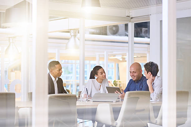 early morning sunrise business meeting in modern office conference room - brightly lit stock photos and pictures