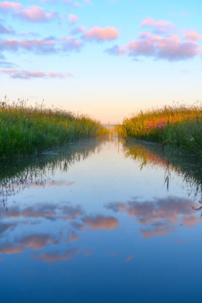 Early morning sunrise over a creek during a beautiful springtime day over the Zwartendijk near Kampen