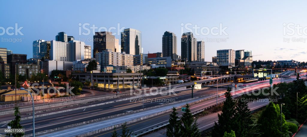 Early Morning Traffic Passes in front Of Buildings Reflecting Sunrise Light in Bellevue, Washington stock photo