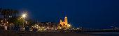 SITGES, Catalonia , SPAIN - JULY 20, 2019: Early morning view of the beach coast in Sitges town near Barcelona in Catalonia,Spain with illuminated Parroquia de Sant Bartomeu i Santa Tecla church.