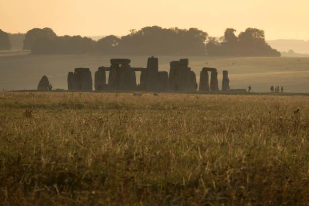 Early morning visitors explore Stonehenge monument Salisbury Plain Wiltshire England stock photo