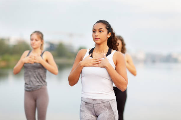 Early morning yoga at lake: touching the heart stock photo