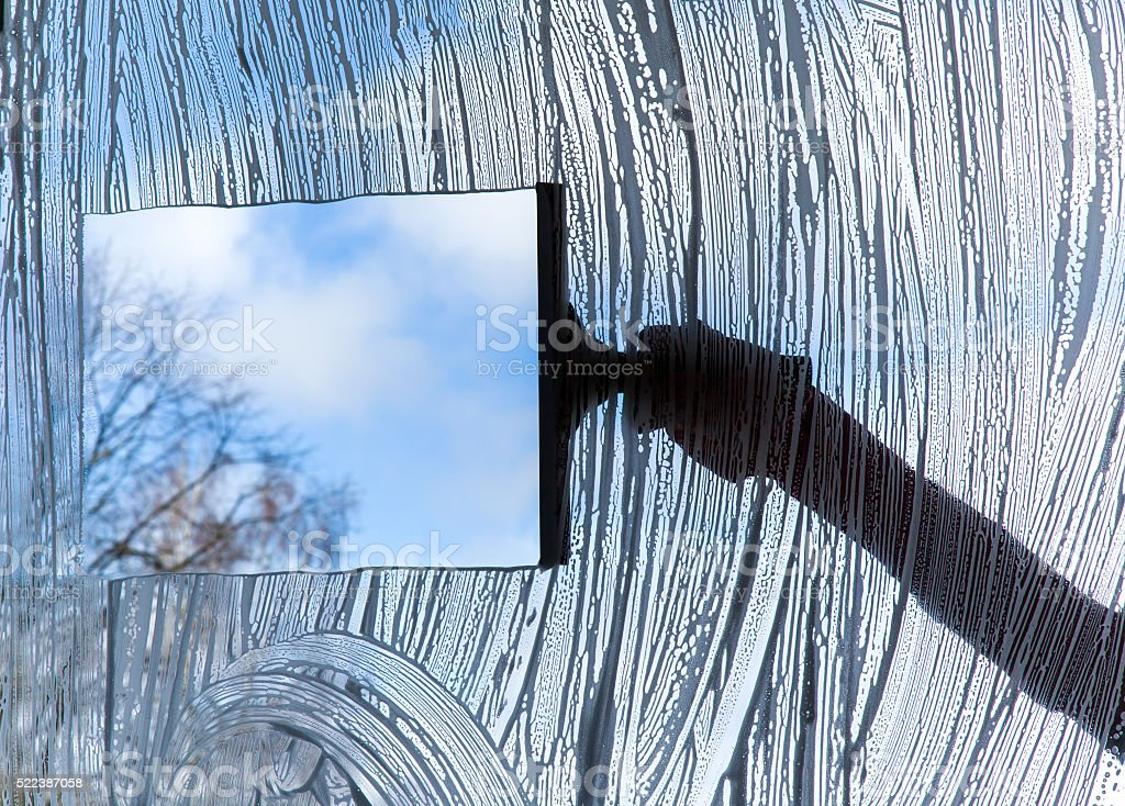 Early spring windows cleaning. Maid cleans window. stock photo