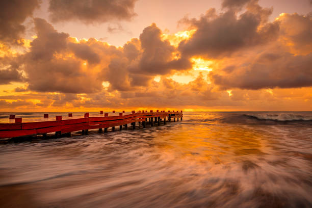 Early Sunrise in the Caribbean Sunrise in the Mayan with crashing waves and orange sun reflecting in the ocean. naya rivera stock pictures, royalty-free photos & images