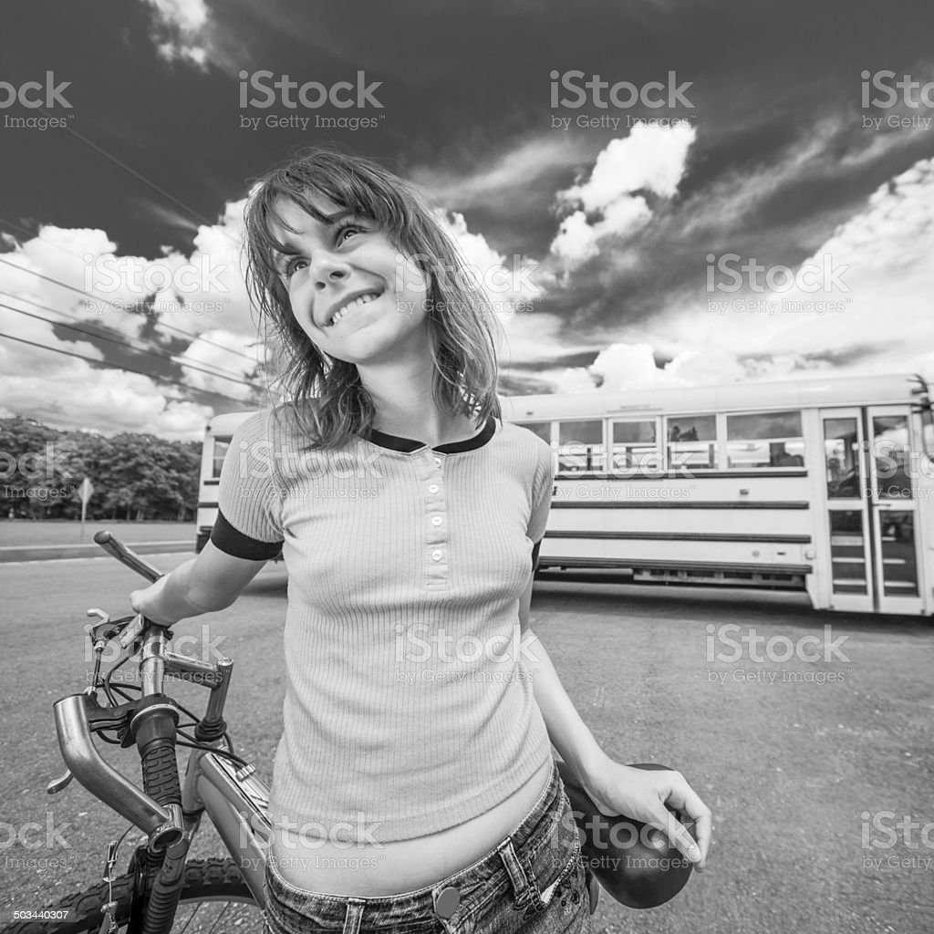 Early teen girl with bicycle in front of school buses stock photo