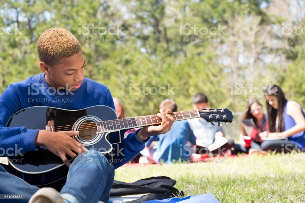 Early teenage boy playing guitar in park with friends. stock photo