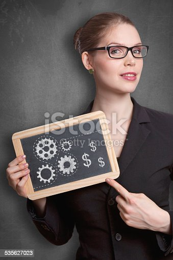 business woman holding black board with cogwheels