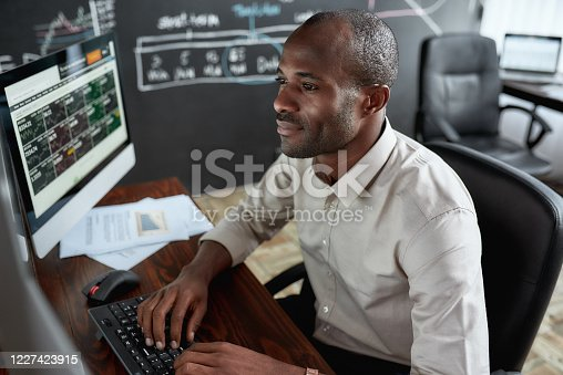Cheerful african male trader sitting by desk and studying analytical reports using pc in the office. Stock trading, people concept. Horizontal shot