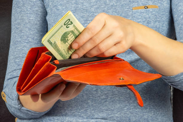 Earn quarantine. Woman puts dollars in a purse stock photo