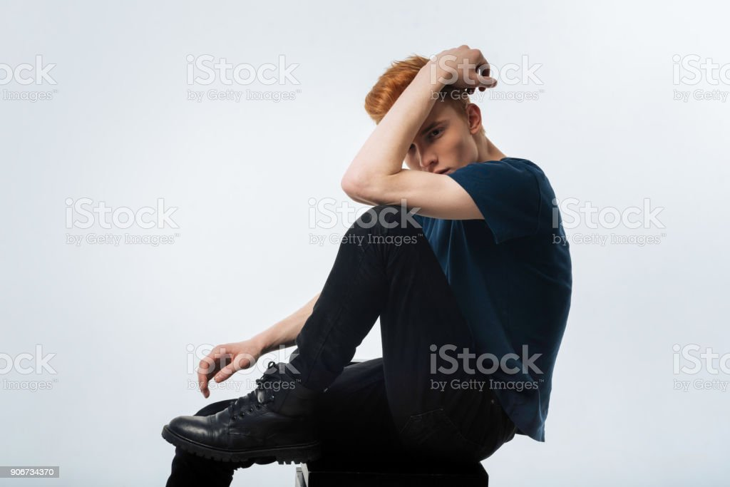 Earnest man hiding his face behind his arm stock photo