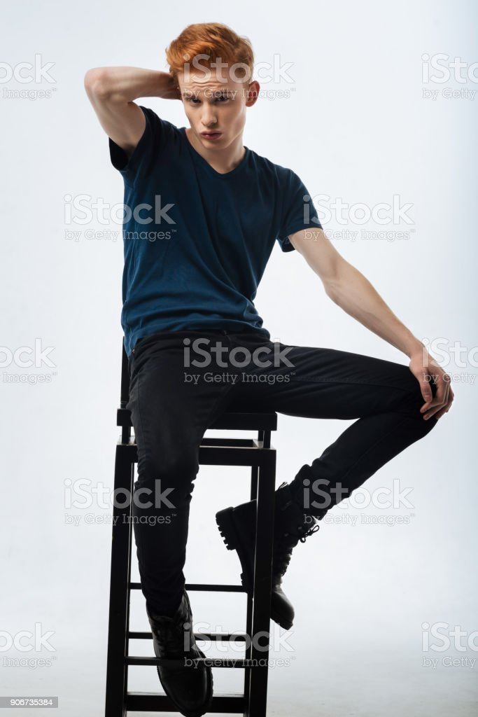 Earnest man sitting on the chair and pouting stock photo