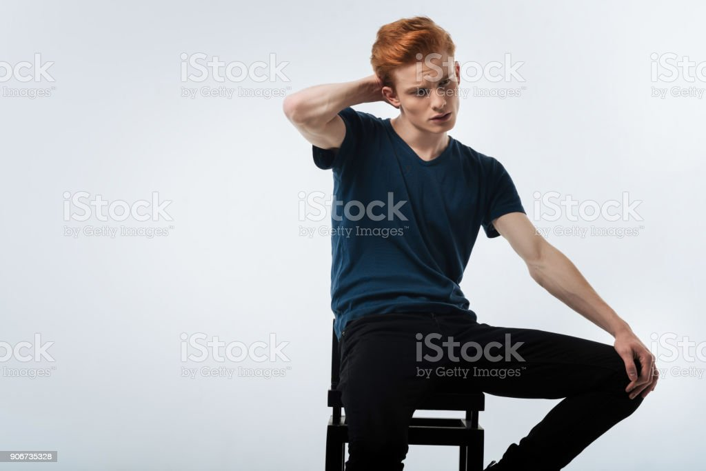 Earnest man sitting on the chair and thinking stock photo