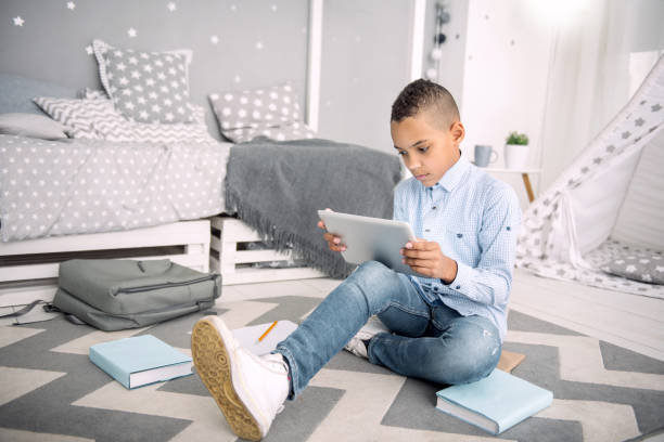 Earnest nice boy involving in online learning Online education. Appealing afro american boy studying task while using tablet absentee stock pictures, royalty-free photos & images