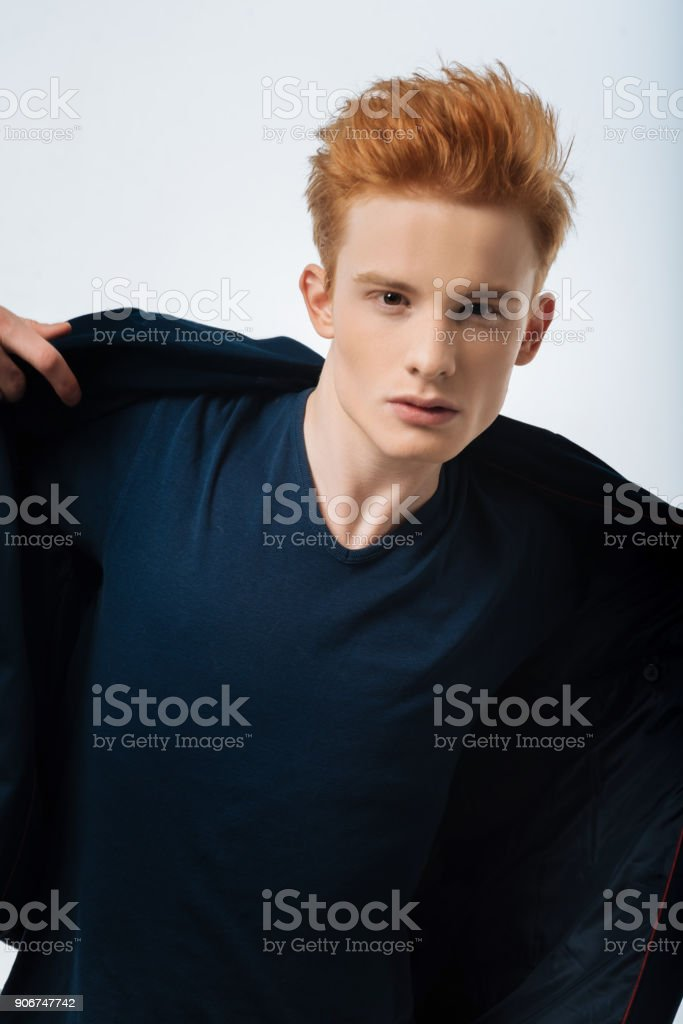Earnest red-headed man putting on his jacket stock photo