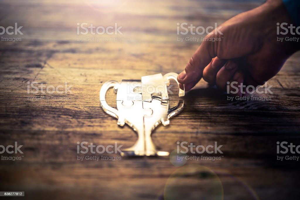 Earning the big trophy piece by piece stock photo