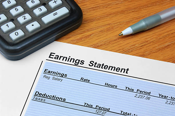 Earnings Statement An itemized earnings statement showing earnings and deductions, on a desk with a calculator and pen. bank statement stock pictures, royalty-free photos & images