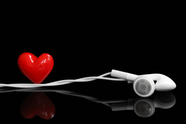 Earphone and a red heart on the black background Earphone and a red heart on the black background with copy space for text auditory cortex stock pictures, royalty-free photos & images