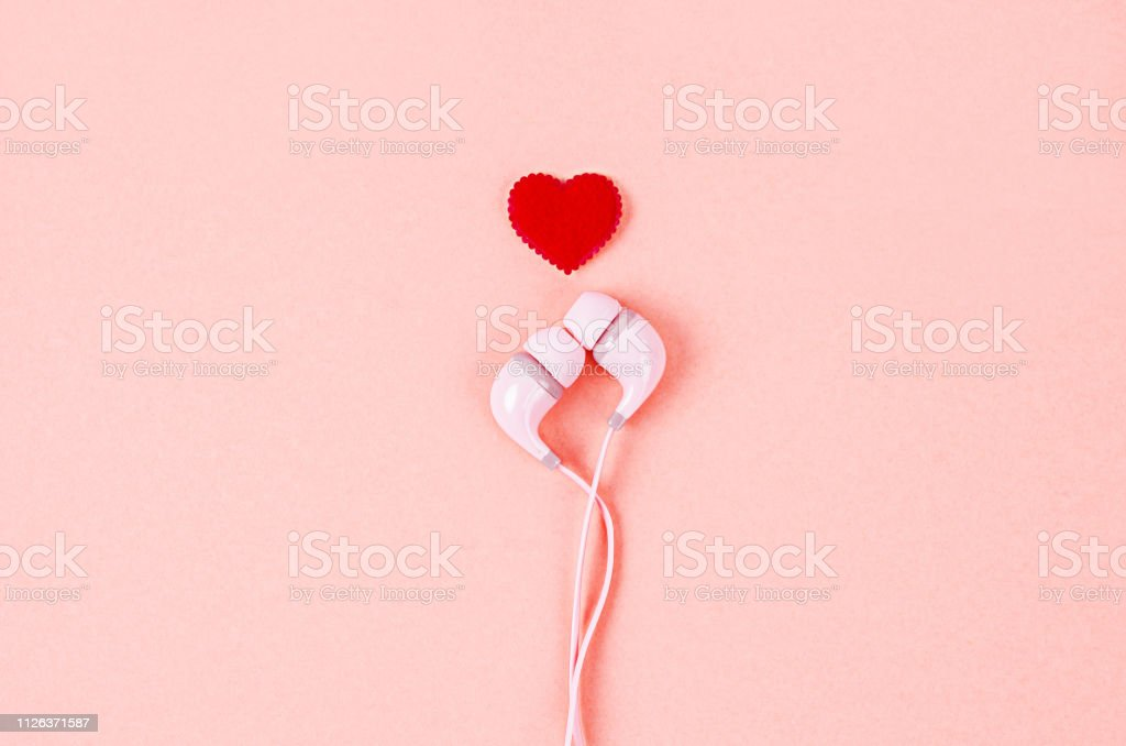 Earphone with red heart on pink background. Earphone with red heart on pink background, Valentine concept. Arts Culture and Entertainment Stock Photo