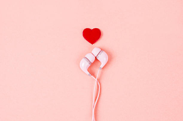 Earphone with red heart on pink background. stock photo