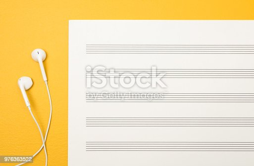 White earphones and blank music paper sheet on vibrant yellow background.
