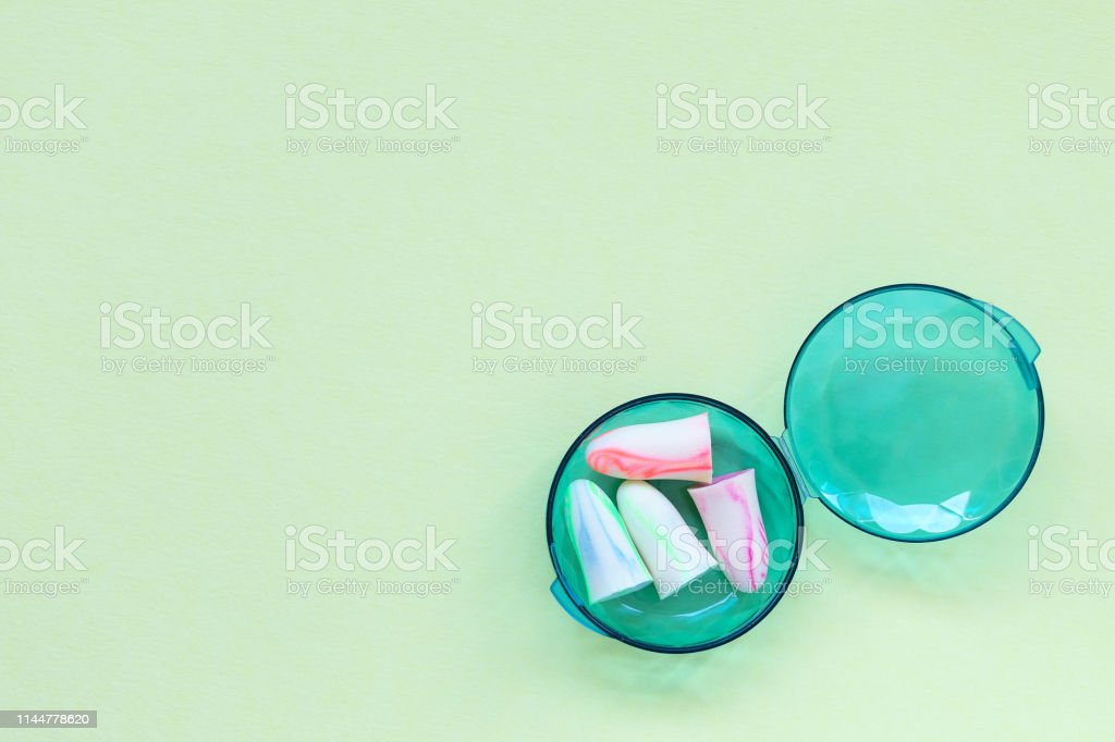 Two pairs of earplugs in a box on the green background. Good sleep...
