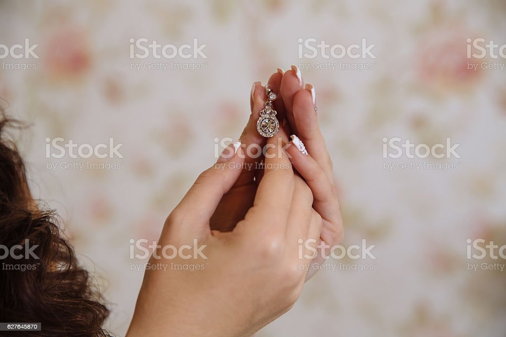 Earrind in the hands of the bride stock photo