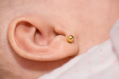 Close-up of a gold earring in a baby's ear