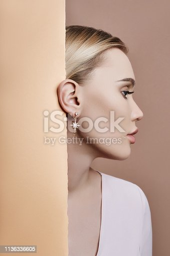 Earrings and jewelry in ear of a sexy blonde woman pressed against the paper beige. Perfect blonde girl, gorgeous mysterious look. Advertising jewelry, beautiful earrings in the girl ear. Copy space