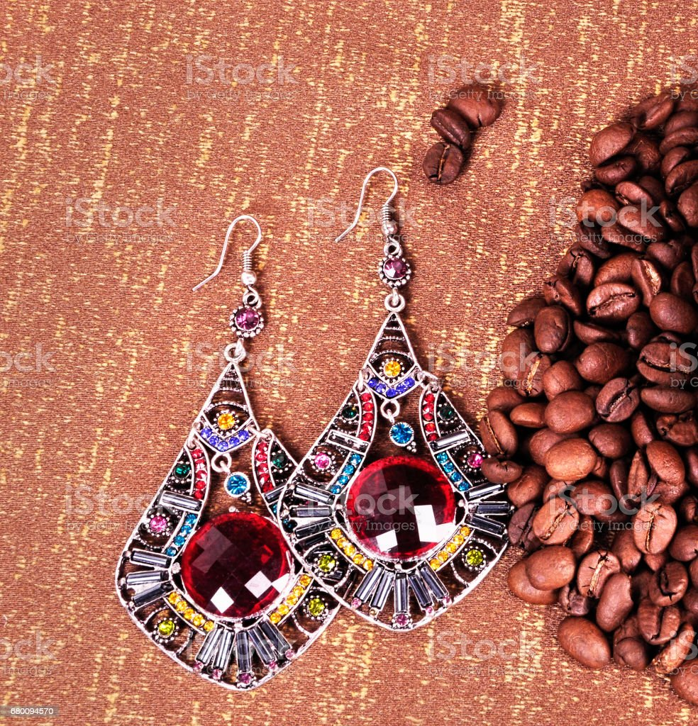 Earrings with multi-colored glass with grains of roasted coffee stock photo