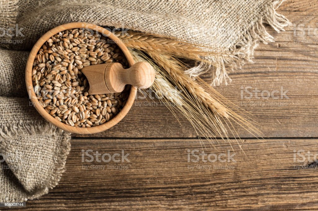 Ears of cereals and bowl of grain. stock photo