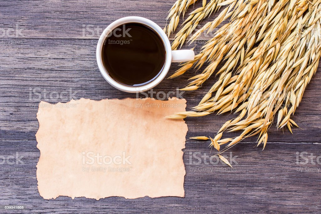 Ears of wheat and old paper on dark wooden table stock photo