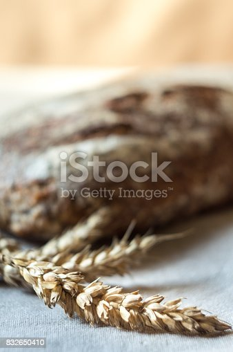 913749618istockphoto Ears of wheat and whole grain bread in background 832650410