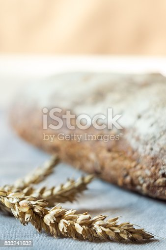 913749618istockphoto Ears of wheat and whole wheat bread in background 833241632