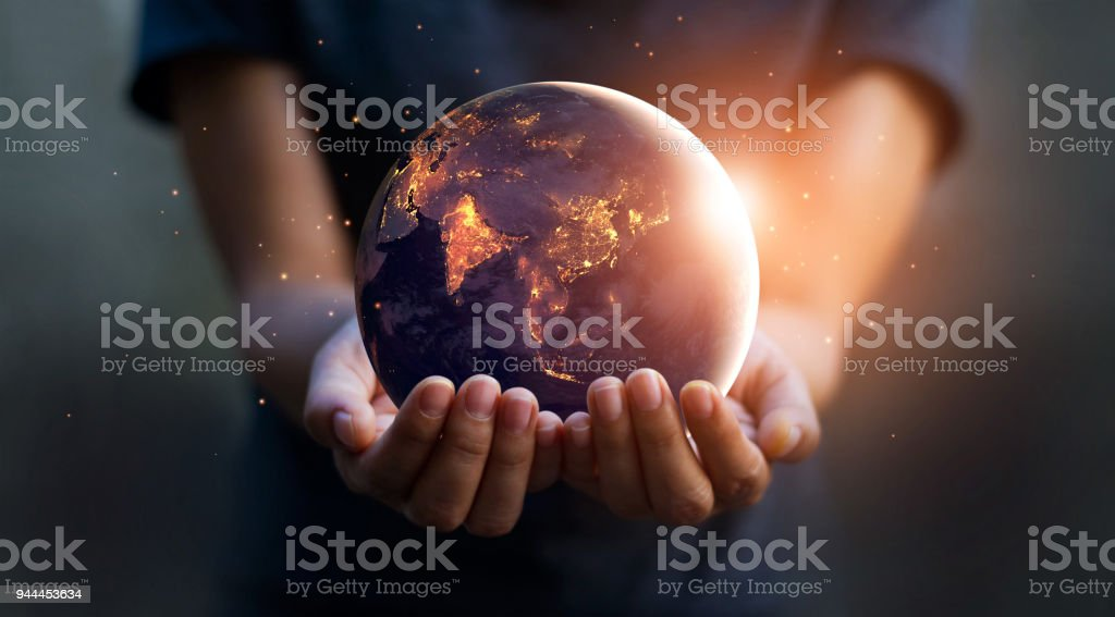 Earth at night was holding in human hands. Earth day. Energy saving concept, Elements of this image furnished by NASA - Zbiór zdjęć royalty-free (Bezpieczeństwo)