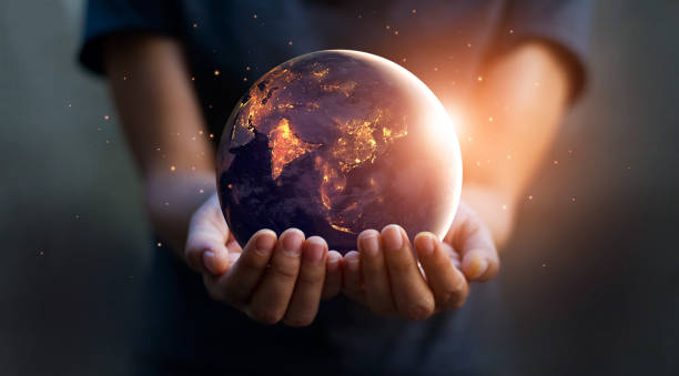 earth at night was holding in human hands. earth day. energy saving concept, elements of this image furnished by nasa - energia rinnovabile foto e immagini stock