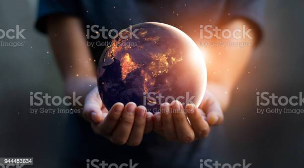 Photo of Earth at night was holding in human hands. Earth day. Energy saving concept, Elements of this image furnished by NASA