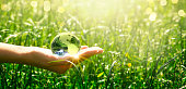 Earth crystal glass globe in human hand on grass background. Saving environment and clean green planet concept. Card for World Earth Day concept.