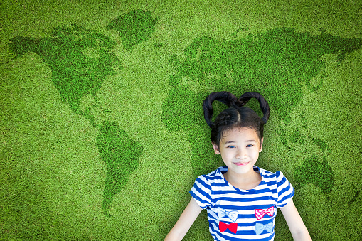 istock Earth day and children's day concept with happy Asian kid relaxing on world map green lawn 955863842