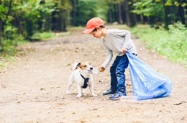 Het dagconcept van de aarde met kind en hond schoonmakend park dat plastic flessen verzamelt foto
